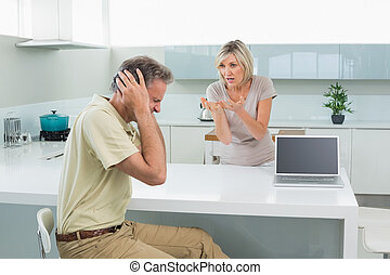 Man covering his ears as woman argue in kitchen - Tired man...