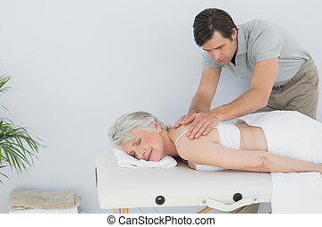 Male physiotherapist massaging a senior womans back in the...