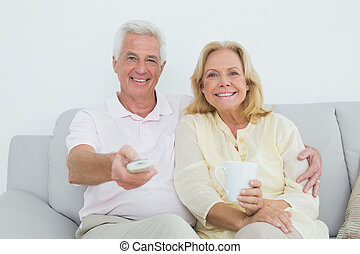 Relaxed cheerful senior couple watching television -...