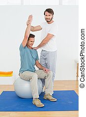 Man on yoga ball working with a phy