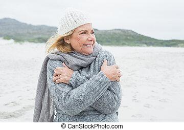 Cheerful senior woman shivering at beach