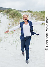 Happy senior woman running at beach - Full length of a happy...