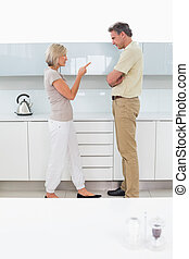 Side view of a couple arguing in kitchen