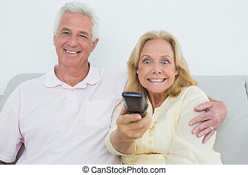 Shocked senior couple watching television - Relaxed shocked...