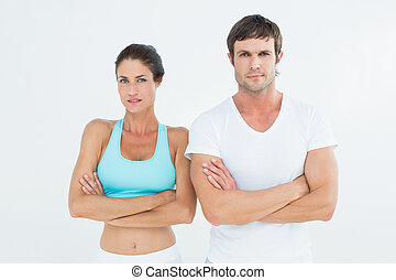 Portrait of a fit young couple with arms crossed