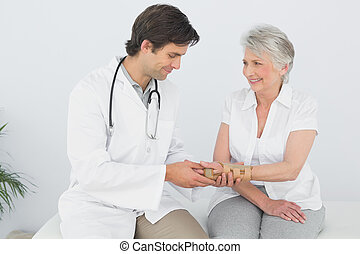 Male physiotherapist examining a senior woman's wrist in the...