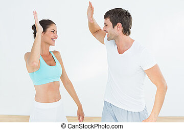 Cheerful fit young couple giving high five in the fitness...