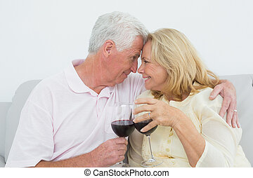 Senior couple toasting wine glasses at home - Relaxed loving...