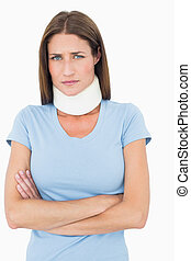 Portrait of a young woman wearing cervical collar over white...