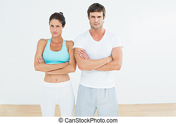 Fit young couple with arms crossed in fitness studio -...