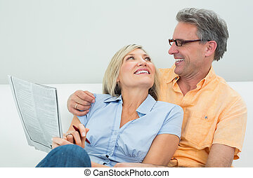 Happy couple with newspaper in the living room
