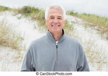 Smiling handsome casual senior man at beach - Portrait of a...