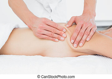 Mid section of a physiotherapist massaging womans body -...