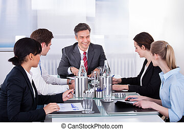 Businesspeople Sitting At Conference Table - Portrait Of...