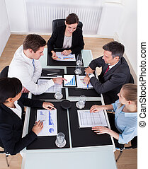 Businesspeople Discussing In Meeting - High Angle View Of...