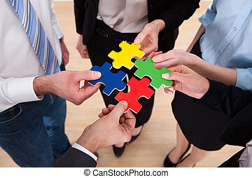 Businesspeople Assembling Jigsaw Puzzle - Close-up Of...