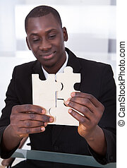 Businessman Holding Jigsaw Puzzle