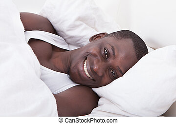 African Man Lying On Bed