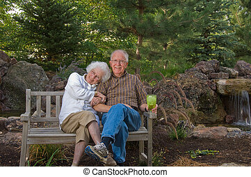 Elderly man and woman sitting on a bench - Senior man and...