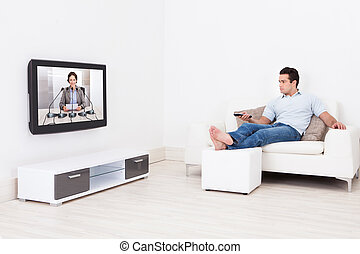 Man Watching Television - Young Man At Home Watching News On...