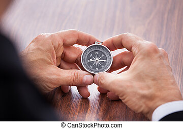 Hand Holding Compass - Close-up Of Hand Holding Compass On...