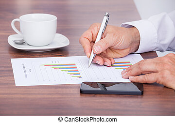 Businessman Writing On Document With Cup And Cellphone On...