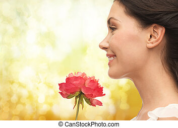 smiling woman smelling flower - picture of smiling woman...