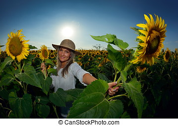 young beautiful woman on blooming sunflower field in summer