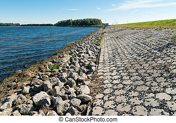 dike and lake - stone dike along a lake in the netherlands
