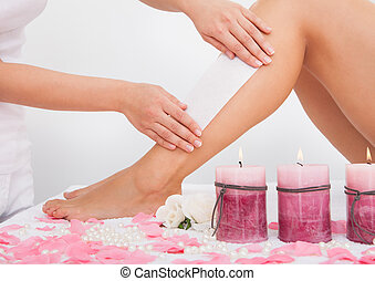 Beautician Waxing A Womans Leg Applying Wax Strip