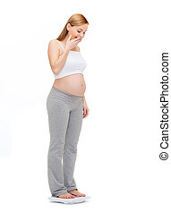 amazed pregnant woman weighting herself - pregnancy,...
