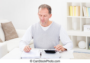 Mature Man Holding Calculator And Bills