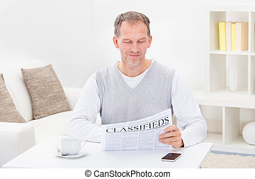 Mature Man Reading Newspaper While Having Coffee