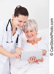 Doctor Showing Digital Tablet To Patient - Young Female...