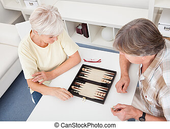 Senior Couple Playing Backgammon - Happy Senior Couple...
