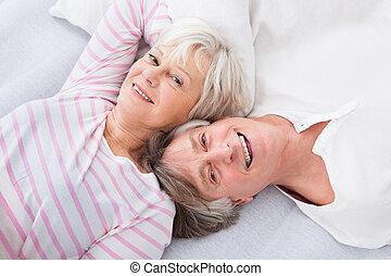 Senior Couple Lying On Bed - Happy Senior Couple Lying Side...