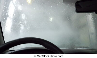 Inside view on windscreen during washing - Water falls down...