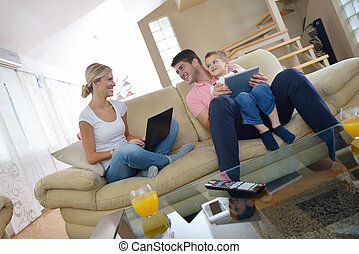 family at home using tablet computer - happy young family...