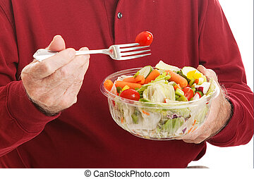 Senior Man Eats Salad - Closeup - Closeup of a senior man...