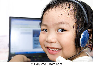 IT education - Young preschool girl, listening to music or a...