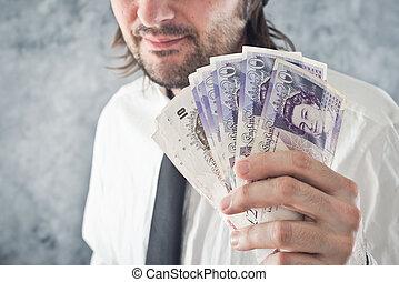 Businessman holding British pounds money