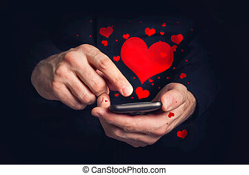 Man typing love text messages on a smartphone for...