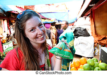 Young Woman buying apples in the market - A young freckled...