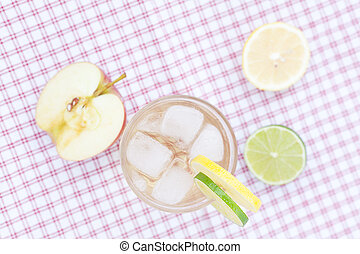 water with lemon and lime,apple in a glass with ice