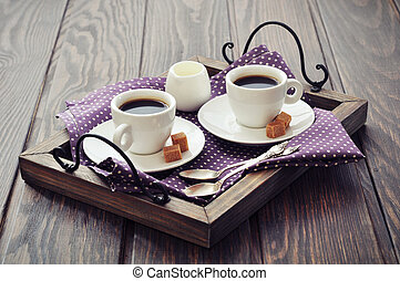 Coffee in cups with spoon and milk on vintage wooden tray