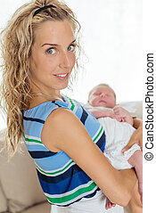 Newborn with a dress in her mother and 39;s arms - Newborn...