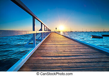 Blue Pier Sunrise - A small jetty sticks out onto the water...