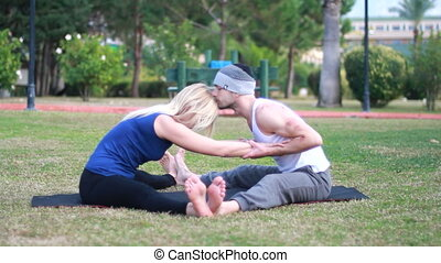 Couples Yoga, man and woman doing yoga exercises in the park