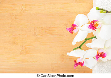 branch orchid and white towels on bamboo wooden  background