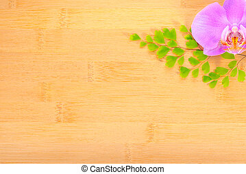 lilac orchid and leaves of fern on bamboo wooden background...